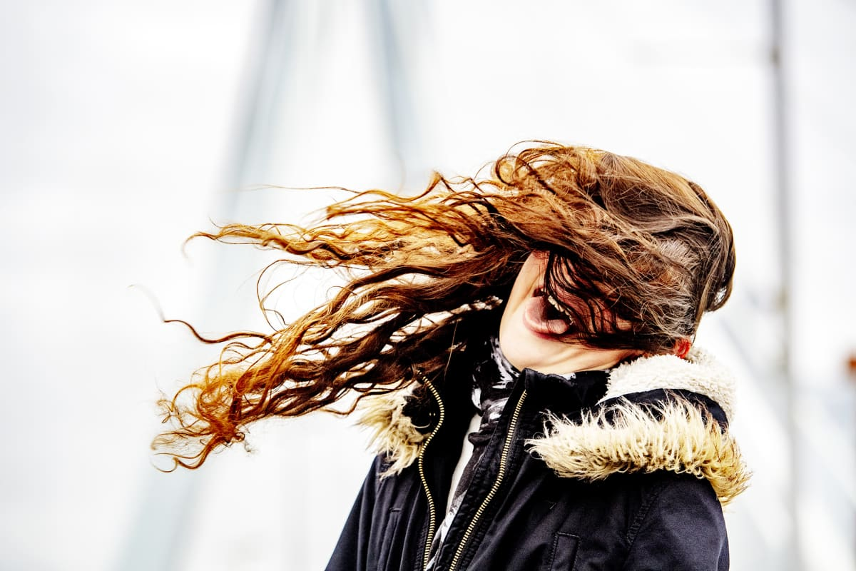 Naisen hiukset hulmuavat tuulessa Rotterdamissa.