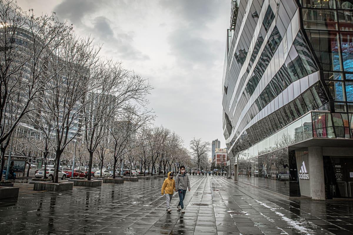 Kaksi suojamaskiin pukeutunutta kävelee autiolla kadulla Pekingissä.