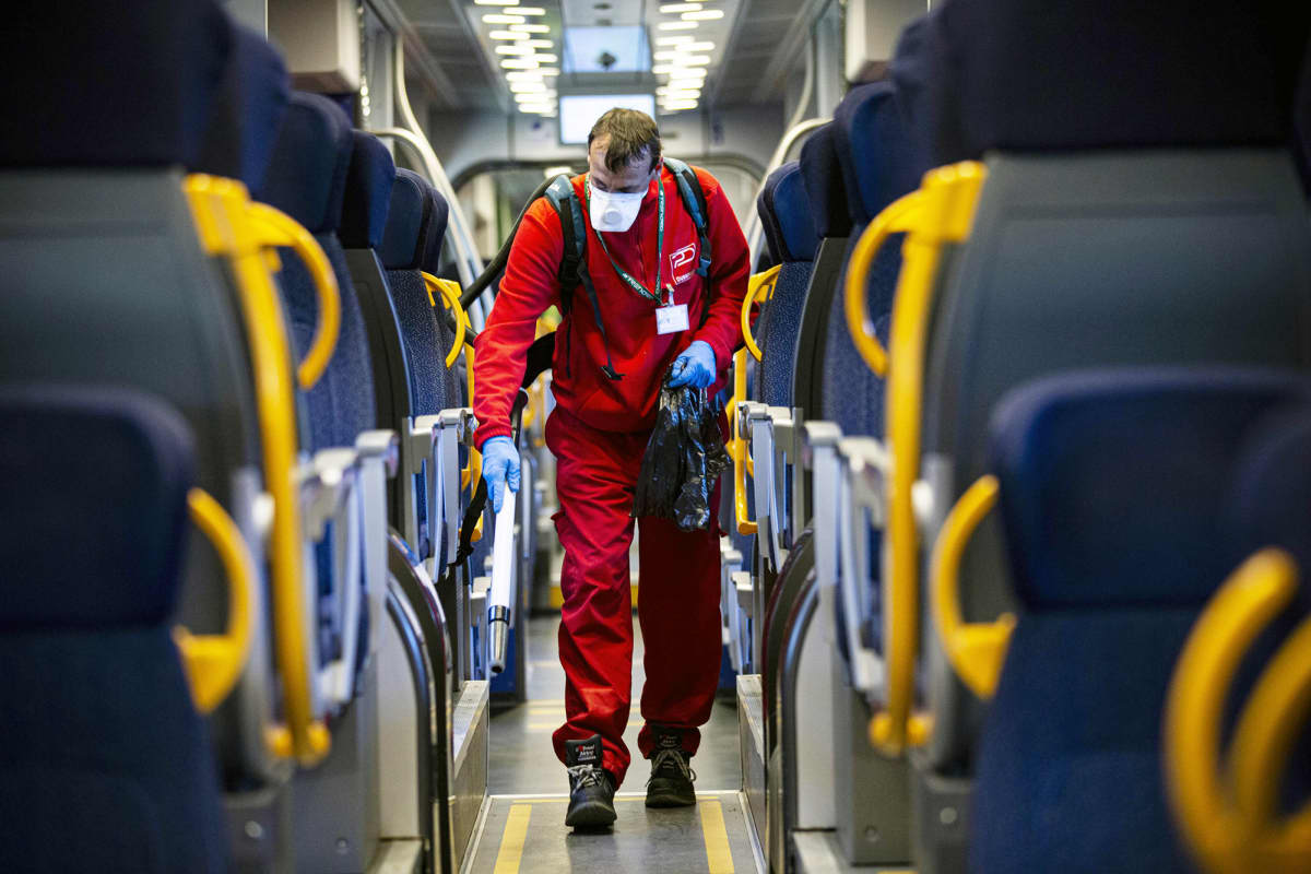 Työntekijä siivoaa ja desinfioi junanvaunua Garibaldin juna-asemalla Milanossa.