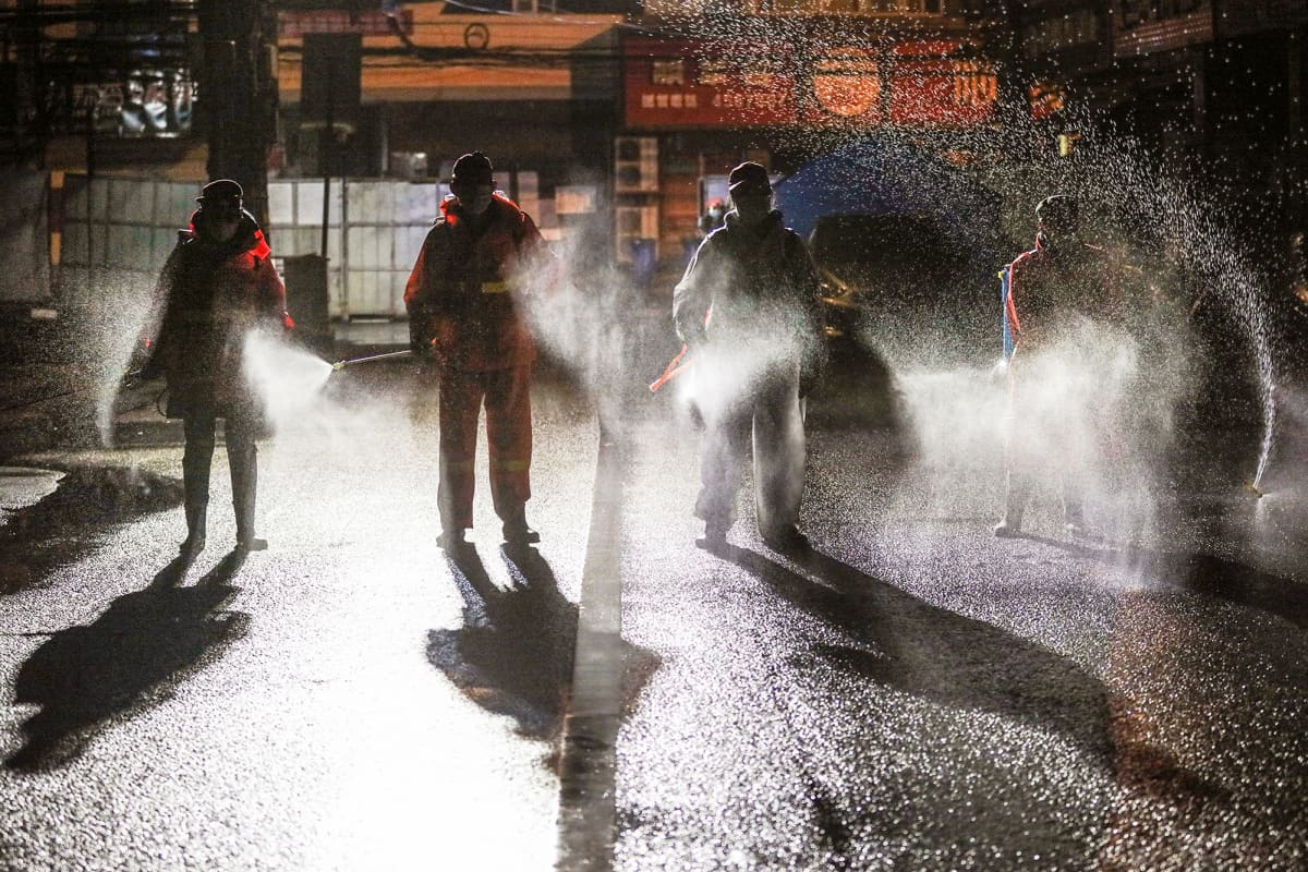 Työntekijät desinfioivat katua Kiinan Xiaoganissa.