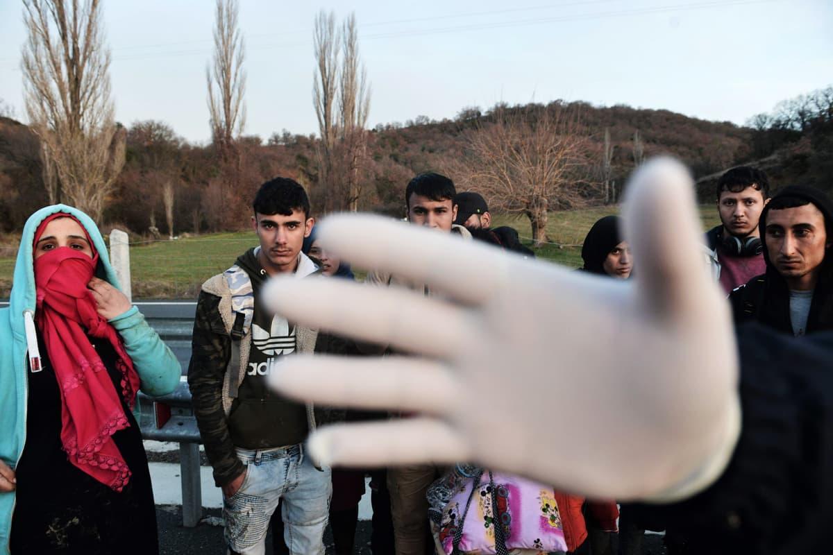 Kuvassa poliisin pidättämät siirtolaiset katsovat kohti kameraa, poliisin käsi on linssin edessä.
