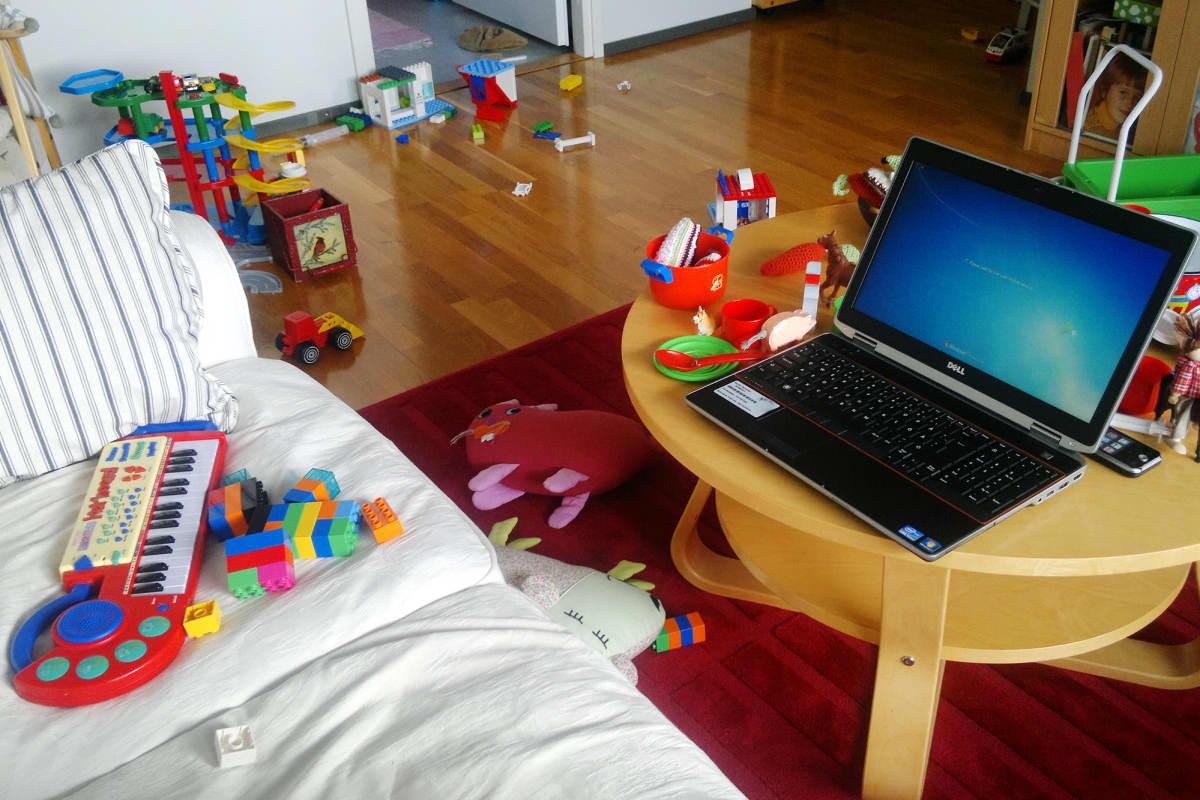 Kannettava tietokone olohuoneessa lelujen keskellä.