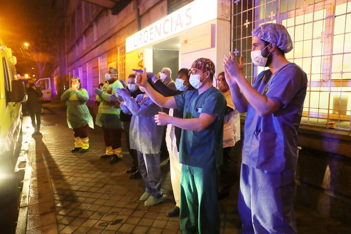 Hoitohenkilöstöön kuuluvat taputtavat sairaalan edustalla Madridissa.