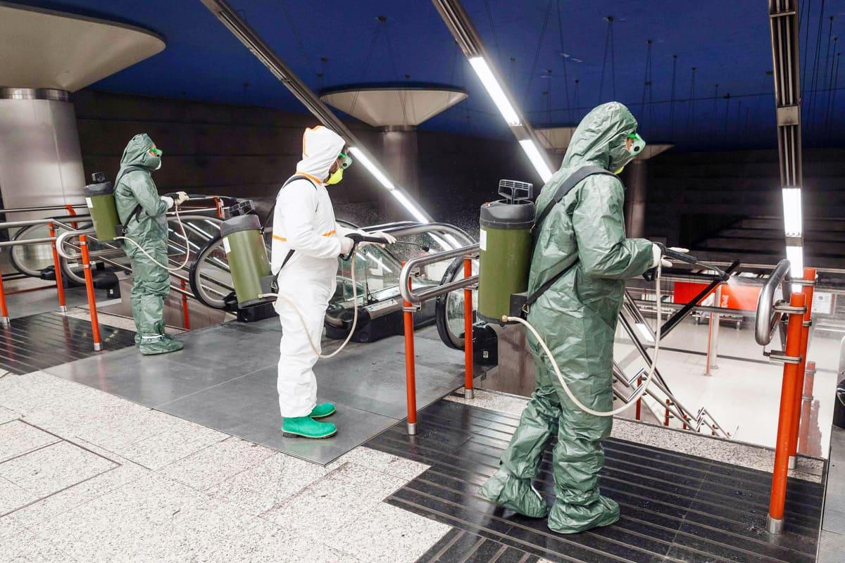 Suojapukuihin pukeutuneet työntekijät desinfioivat metroasemaa Madridissa.