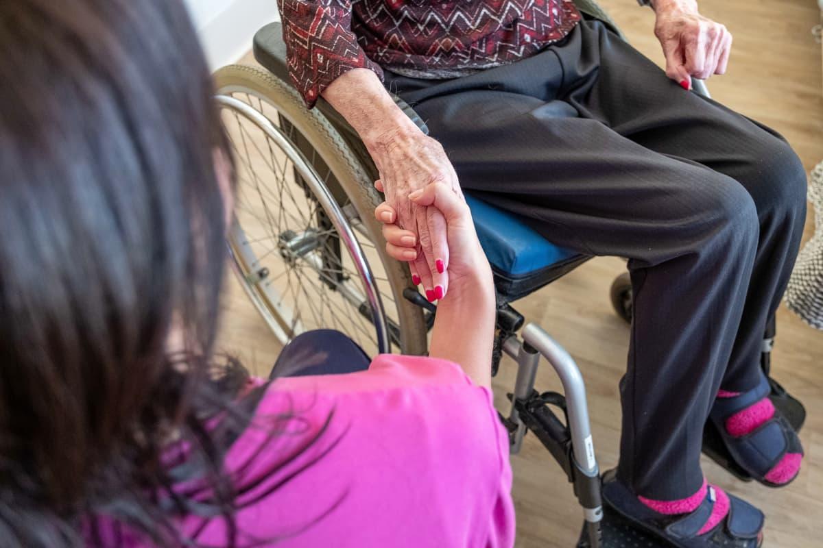 Hoitaja pitää vanhusta kädestä.