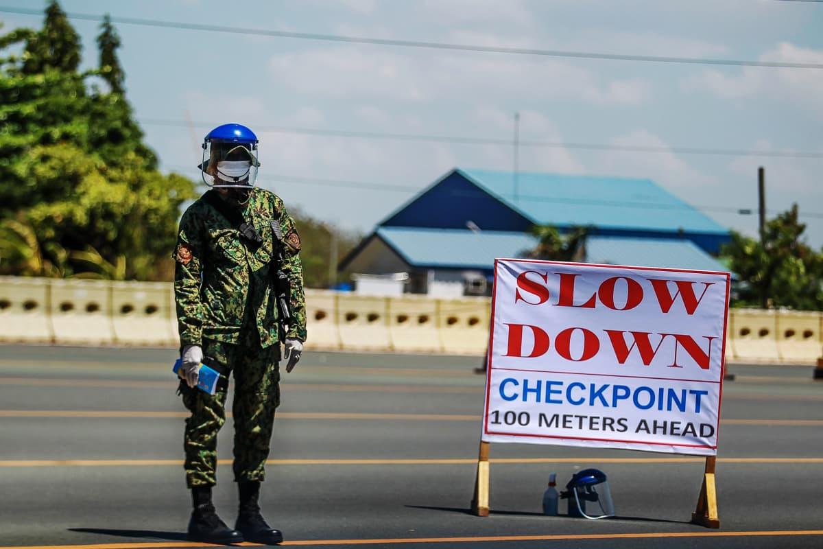 Filippiiniläinen poliisi töissä tien varressa.