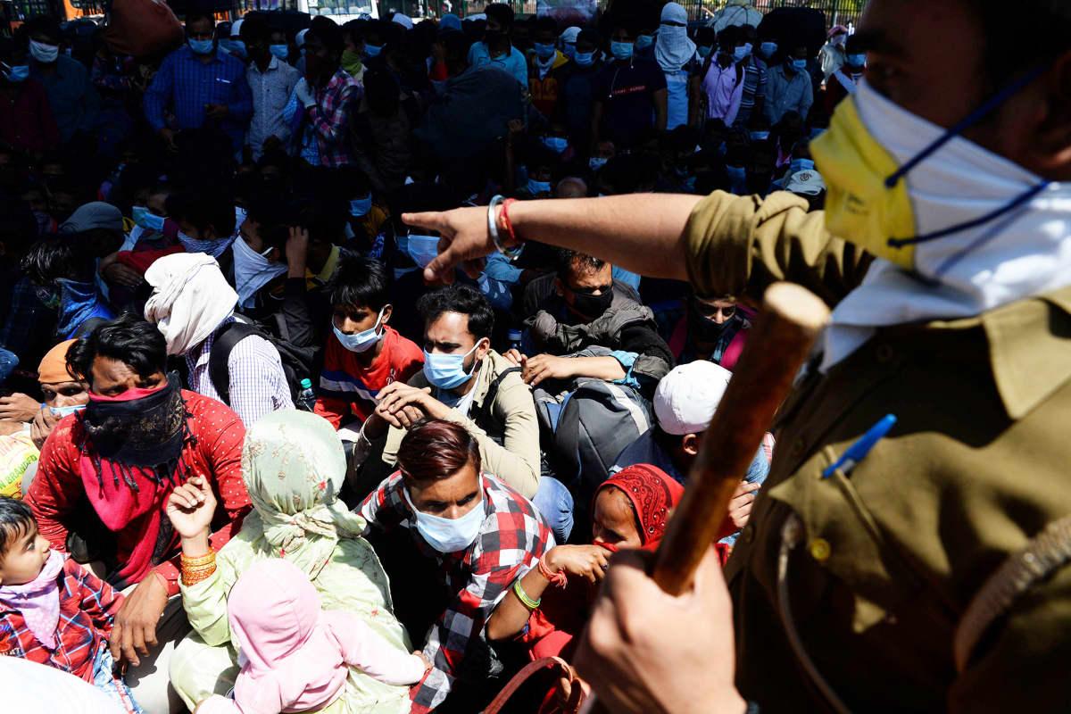 Poliisi ohjaa ihmismassaa Anandan bussiterminaalissa New Delhissä.