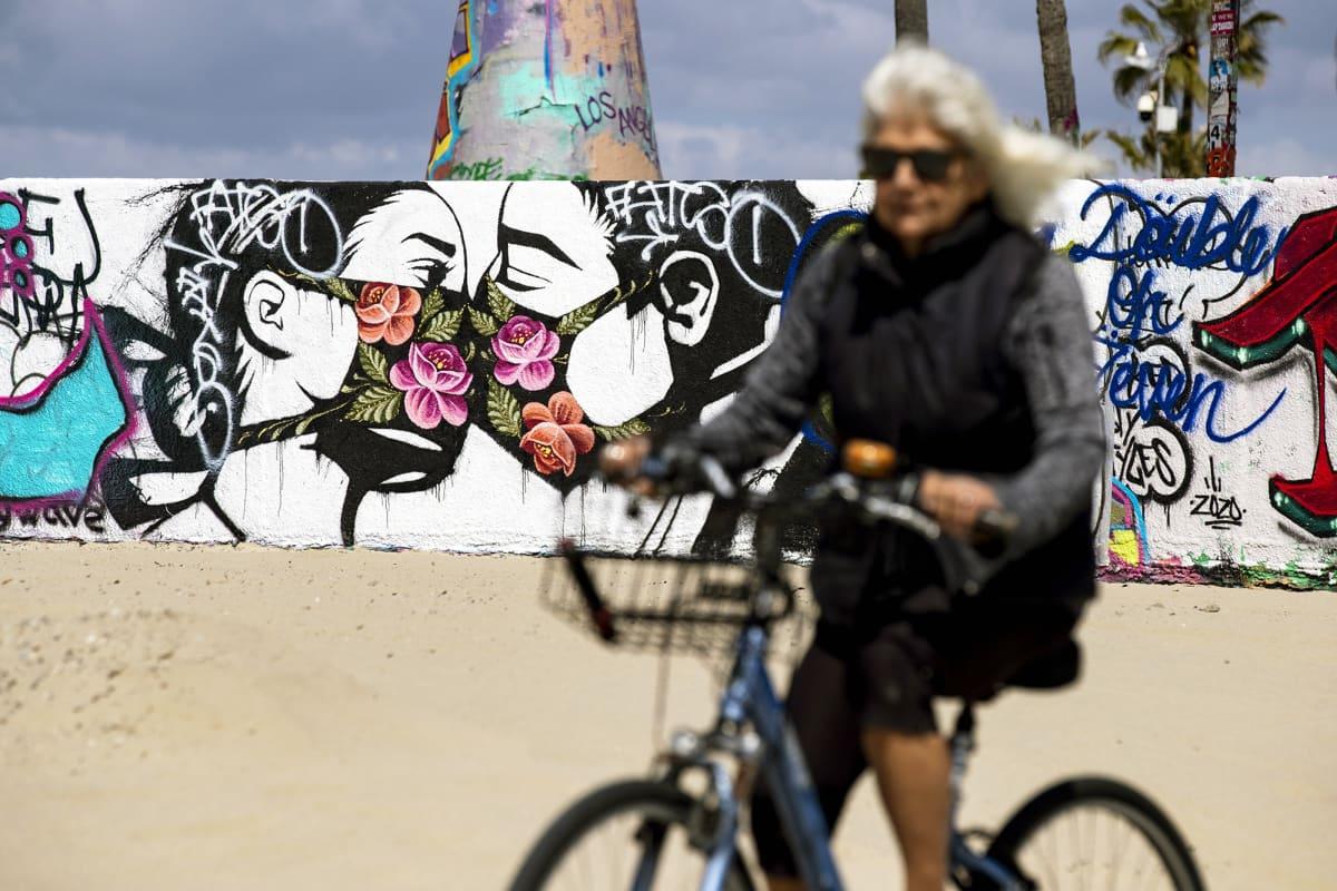 Kasvosuojiin pukeutunut pariskunta suutelee seinämaalauksessa Kaliforniassa.