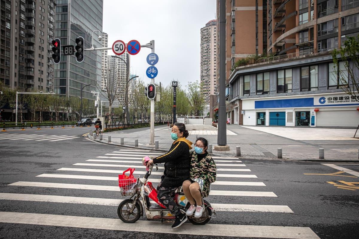 Kasvosuojaan pukeutunut mies kyyditsee mopolla kasvosuojaan pukeutunutta naista Kiinan Wuhanissa.