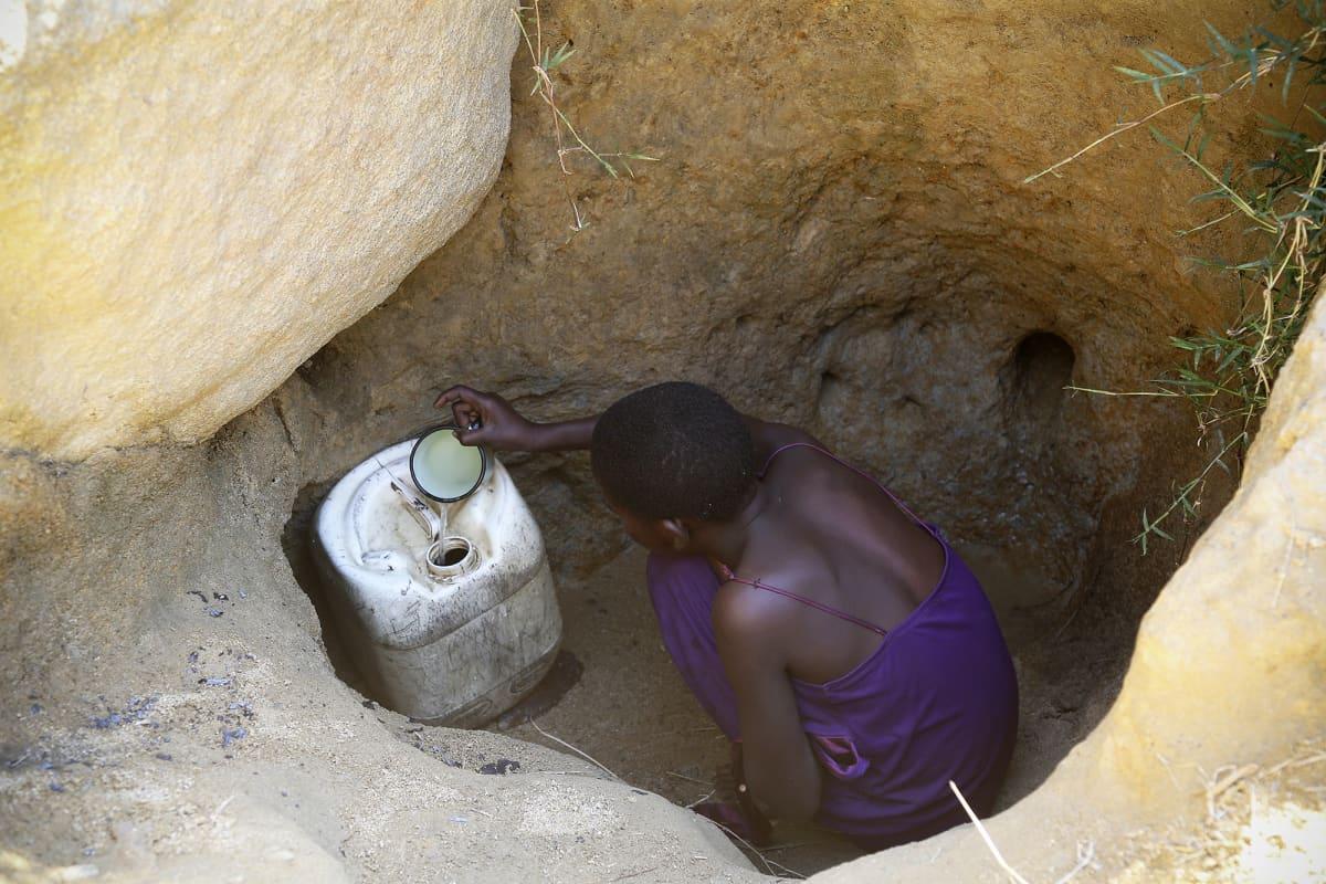 Zimbabwelainen tyttö kerää juomavettä onkalosta.