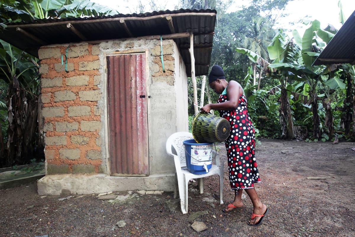 Liberialainen nainen kaataa vettä sankoon pestäkseen kätensä ulkokäymälän edustalla.