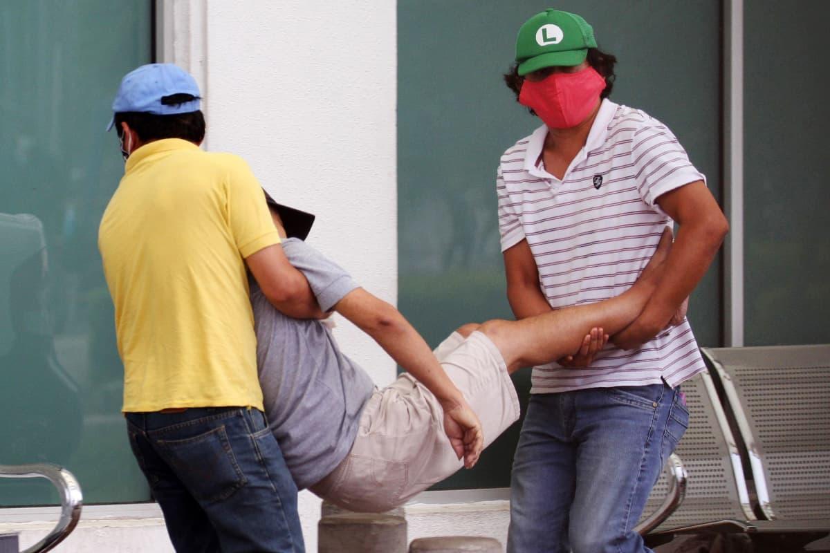 Tuntemattomat miehet kantoivat keskiviikkona sairasta henkilöä sairaalaan Guayaquilin kaupungissa, Ecuadorissa.