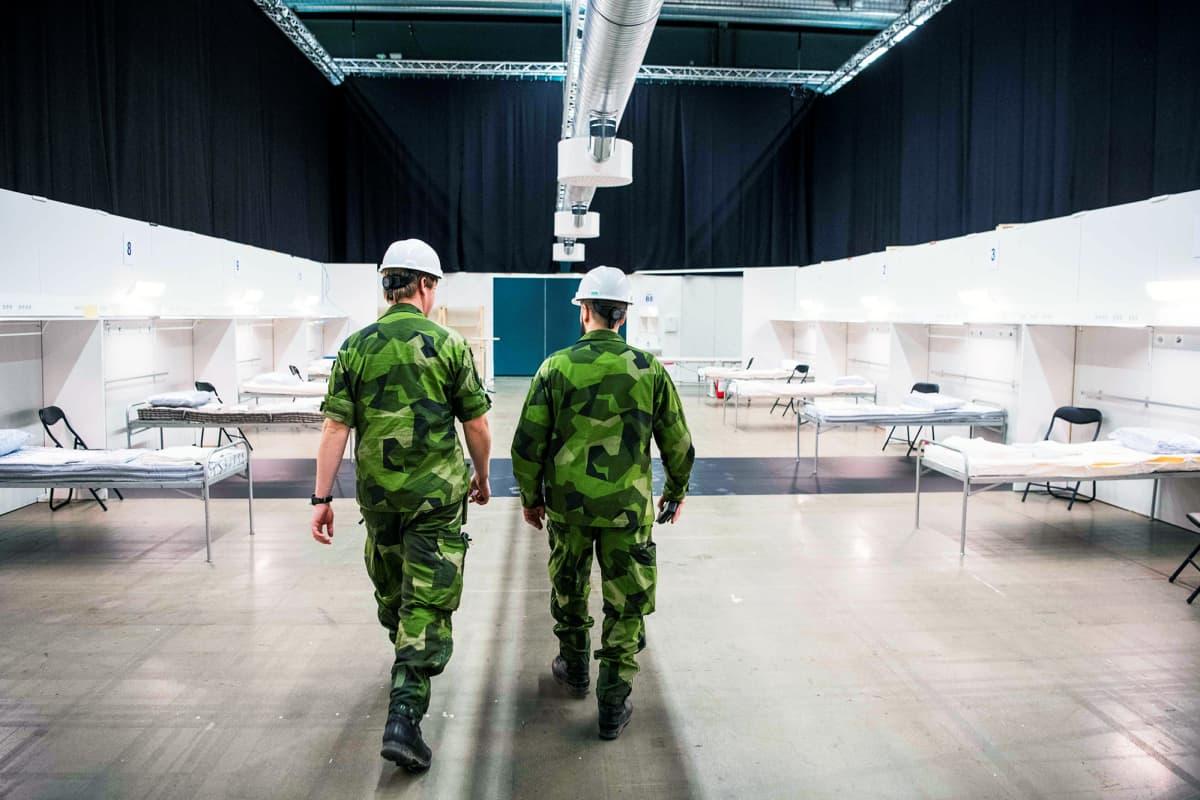 Ruotsin armeijan henkilökuntaa kävelee messukeskukseen rakenteilla olevassa kenttäsairaalassa Tukholmassa.