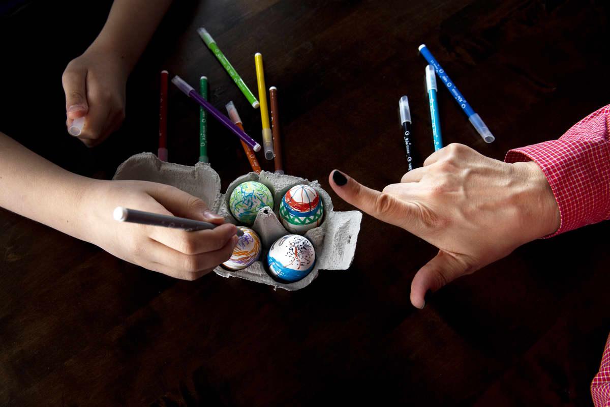 Lapsi koristelee pääsiäismunia, aikuinen osoittaa sormellaan vieressä.