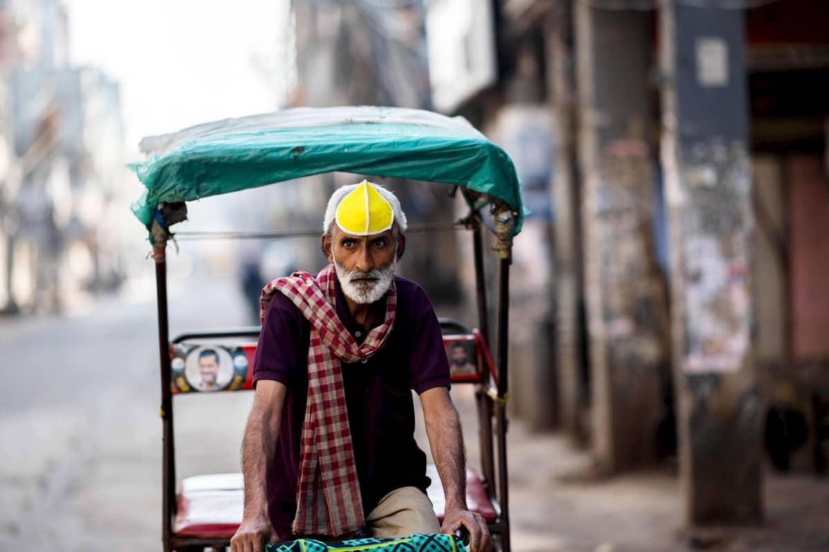 Riksakuski odottaa asiakkaita autiolla kadulla Intian pääkaupungissa New Delhissä.
