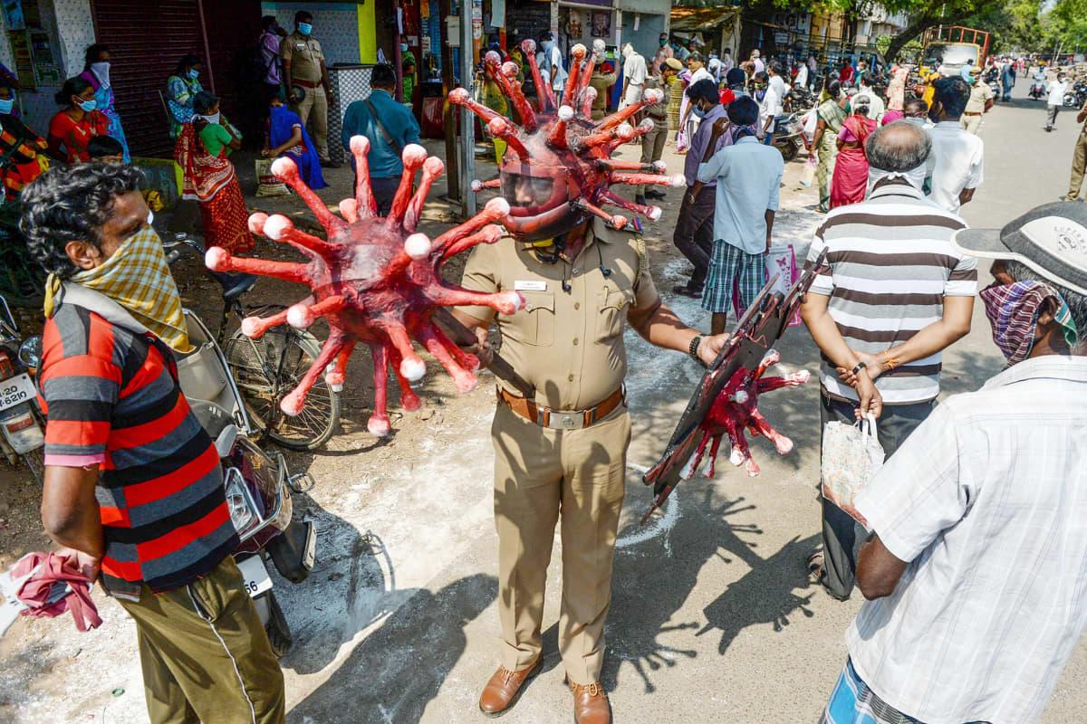 Intialainen poliisi pukeutuneena koronavirusta mallintavaan kypärään.