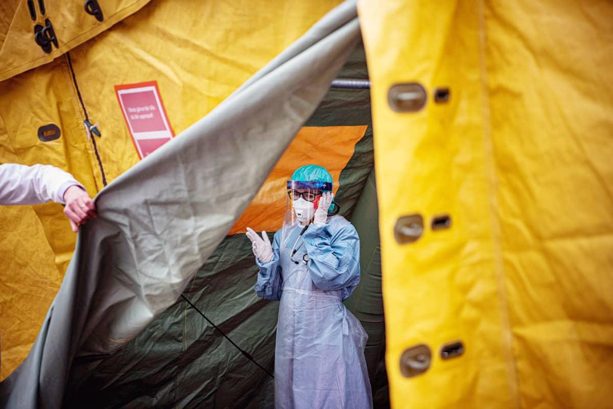 Suojavaruseisiin pukeutunut hoitaja puhuu puhelimeen koronatestejä varten pystytetyssä teltassa Tukholmassa.