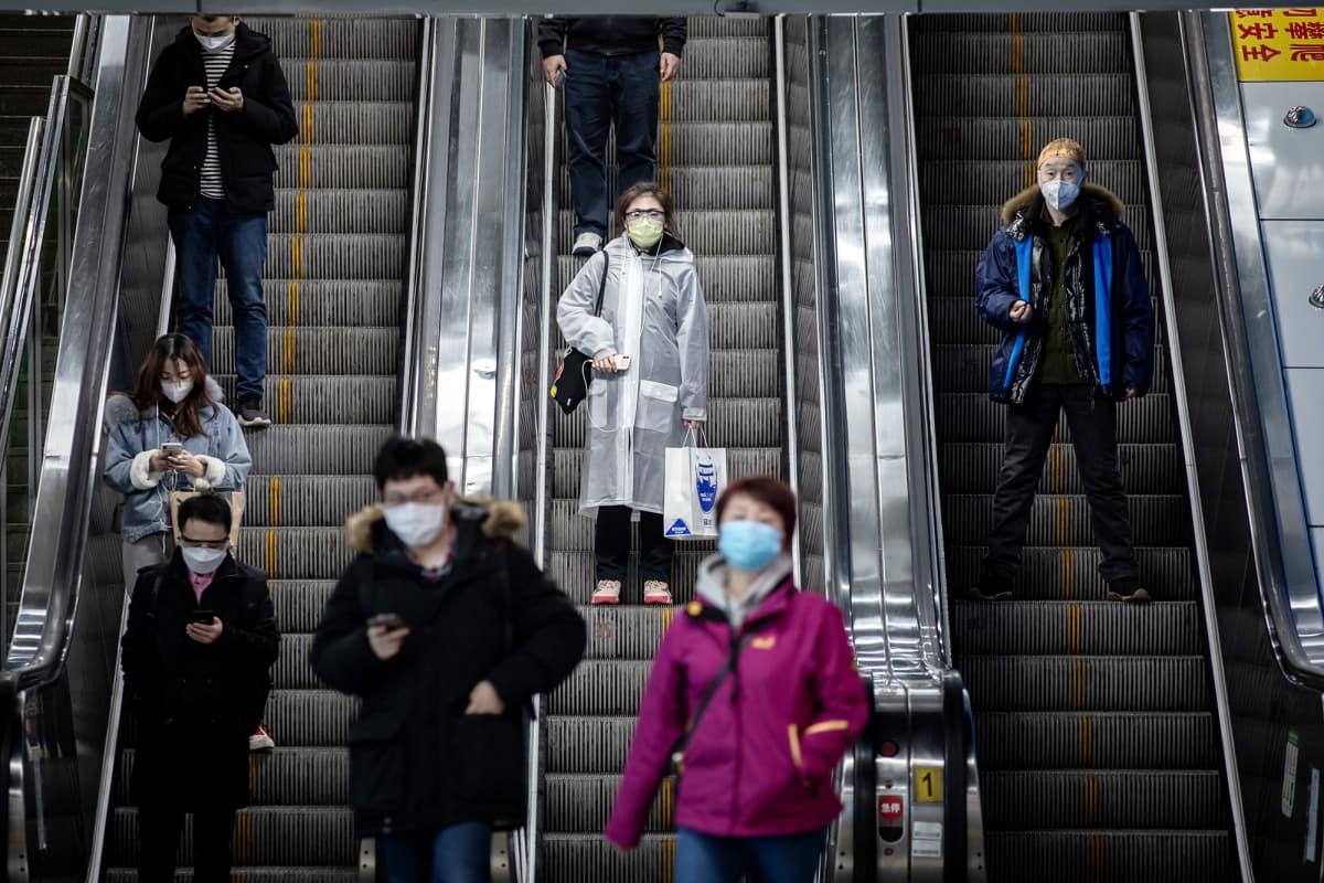 Hengityssuojiin pukeutuneita matkustajia metron rullaportaissa Shanghaissa.