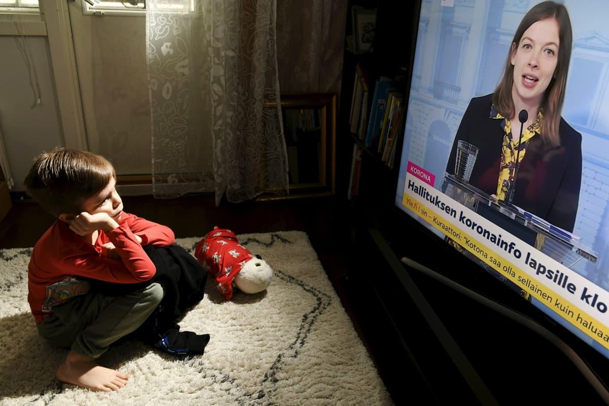 Ekaluokkalainen lapsi katsoo hallituksen lapsille järjestämää koronainfoa kotonaan Espoossa.