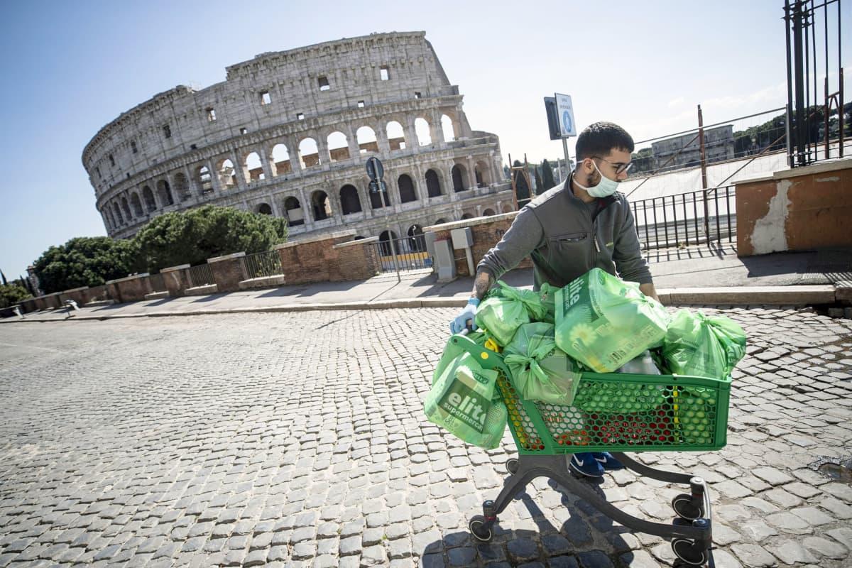 Mies työntää ostoskärryjä autiolla turistialueella Roomassa.