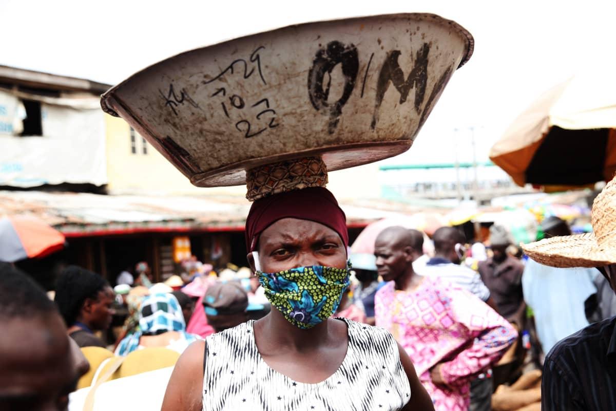 Kuvassa on hengityssuojaa käyttävä nainen nigerialaisella torilla.