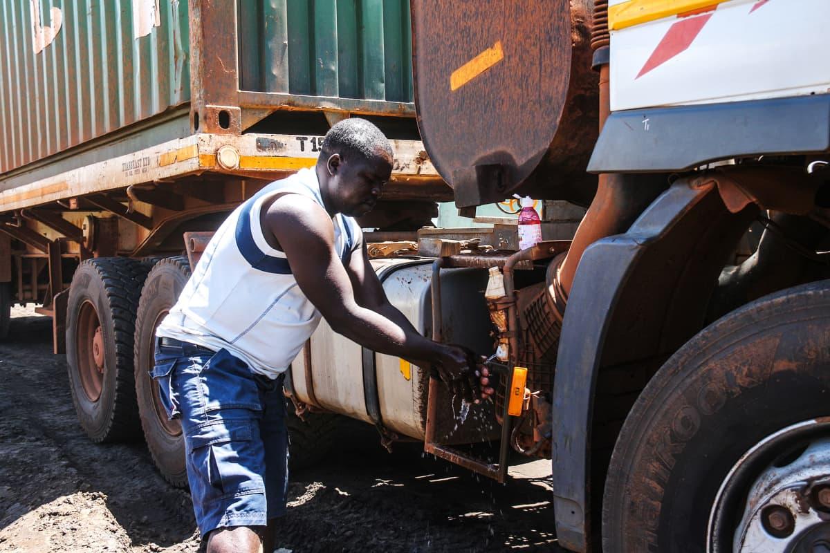 Rekkakuski Benard Masibo pesee kätensä Keniassa vedellä ja saippualla tien päällä.