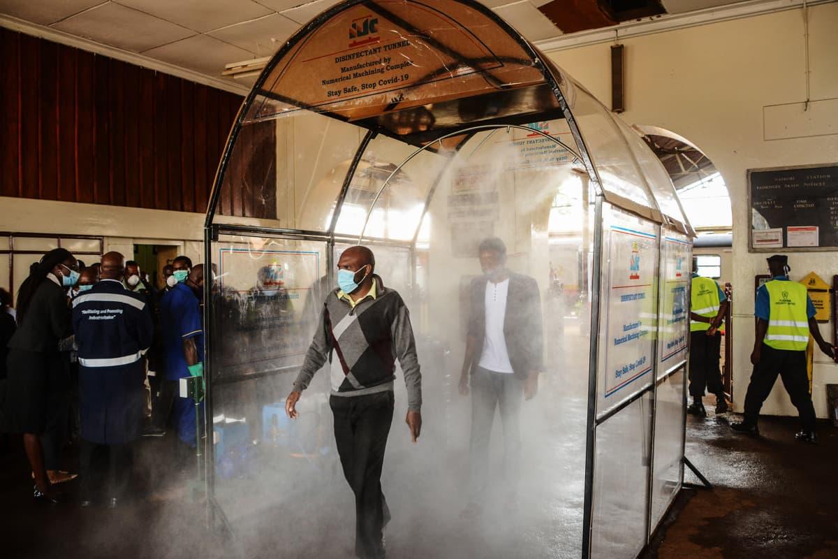 Kuvassa kenialaiset työmatkalaiset kävelevät desinfiointitunnelin läpi juna-asemalla.