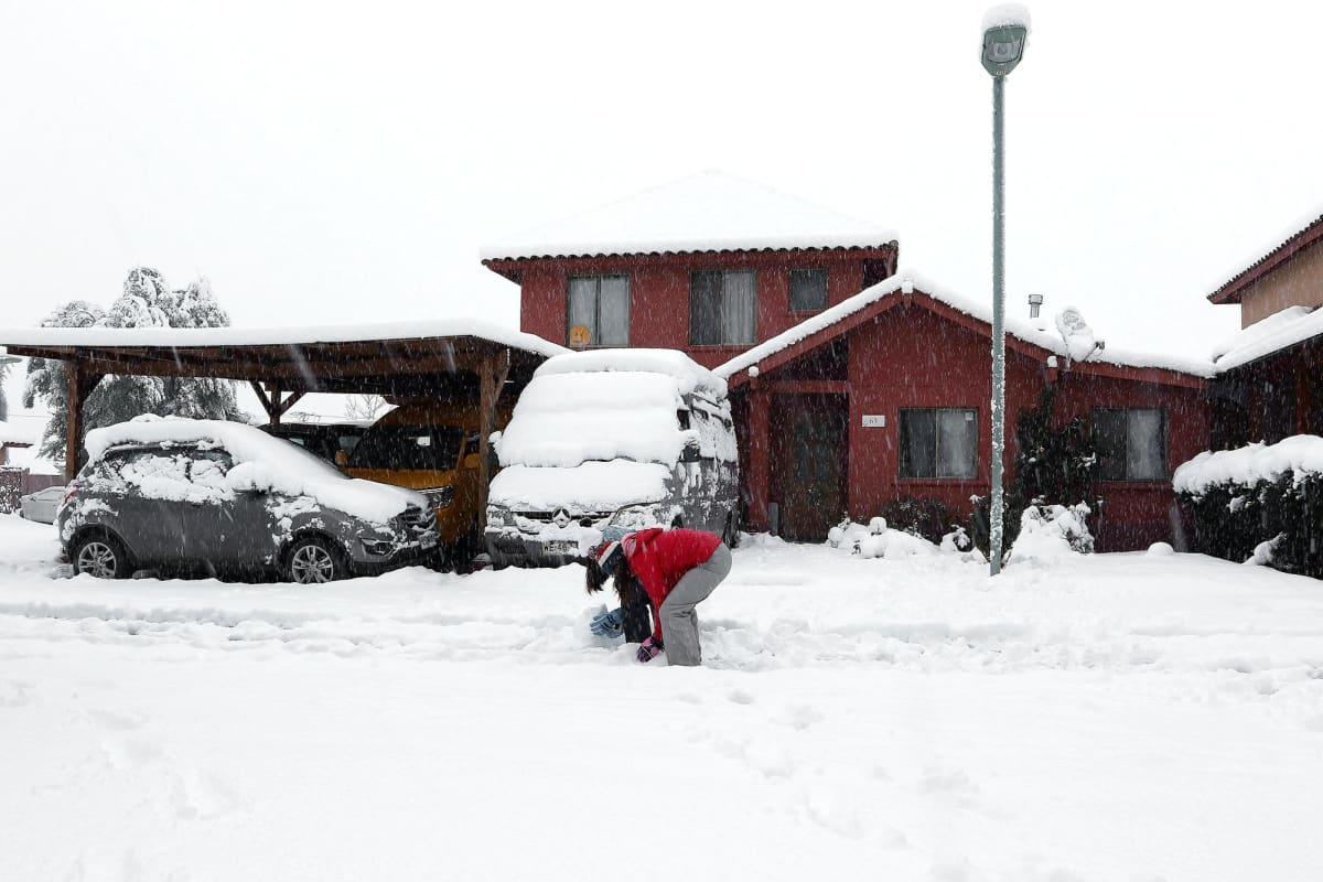 Nainen leikkiii lumihangessa Chilen Santiagossa.