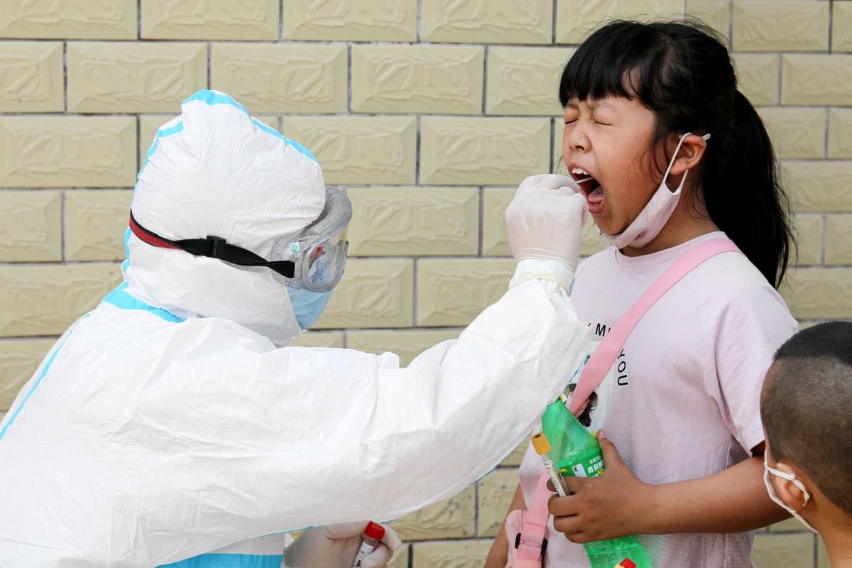Suojapukkuun pukeutunut työntekijä ottaa koronavirusnäytteen lapselta.