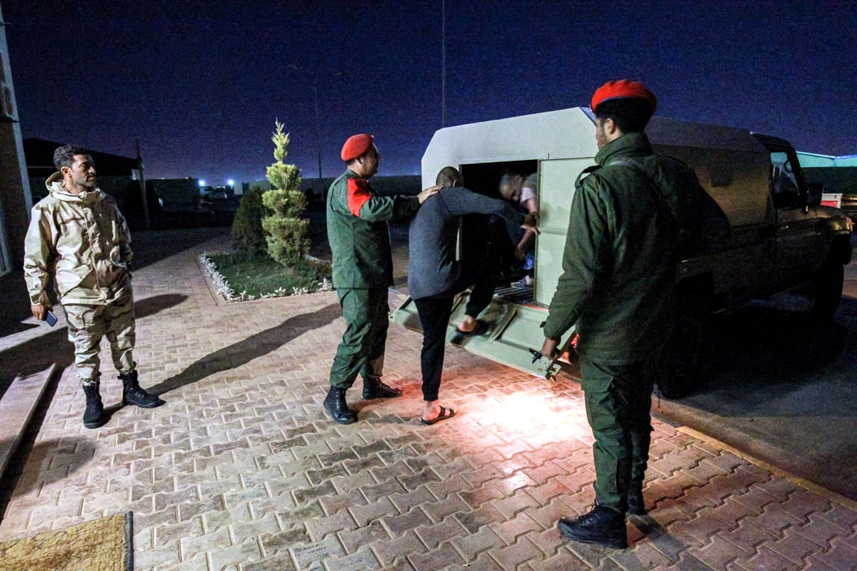 Khalifa Haftarin joukot siirtävät vankeja autoon Libyan Benghazissa.