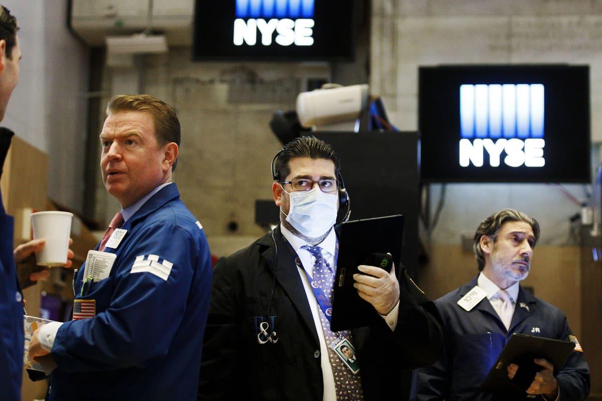 Kuvassa on hengityssuojainta käyttävä meklari New Yorkin pörssissä.