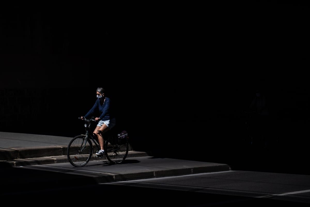 Tummanpuhuvassa kuvassa nainen pyöräilee Pariisissa.