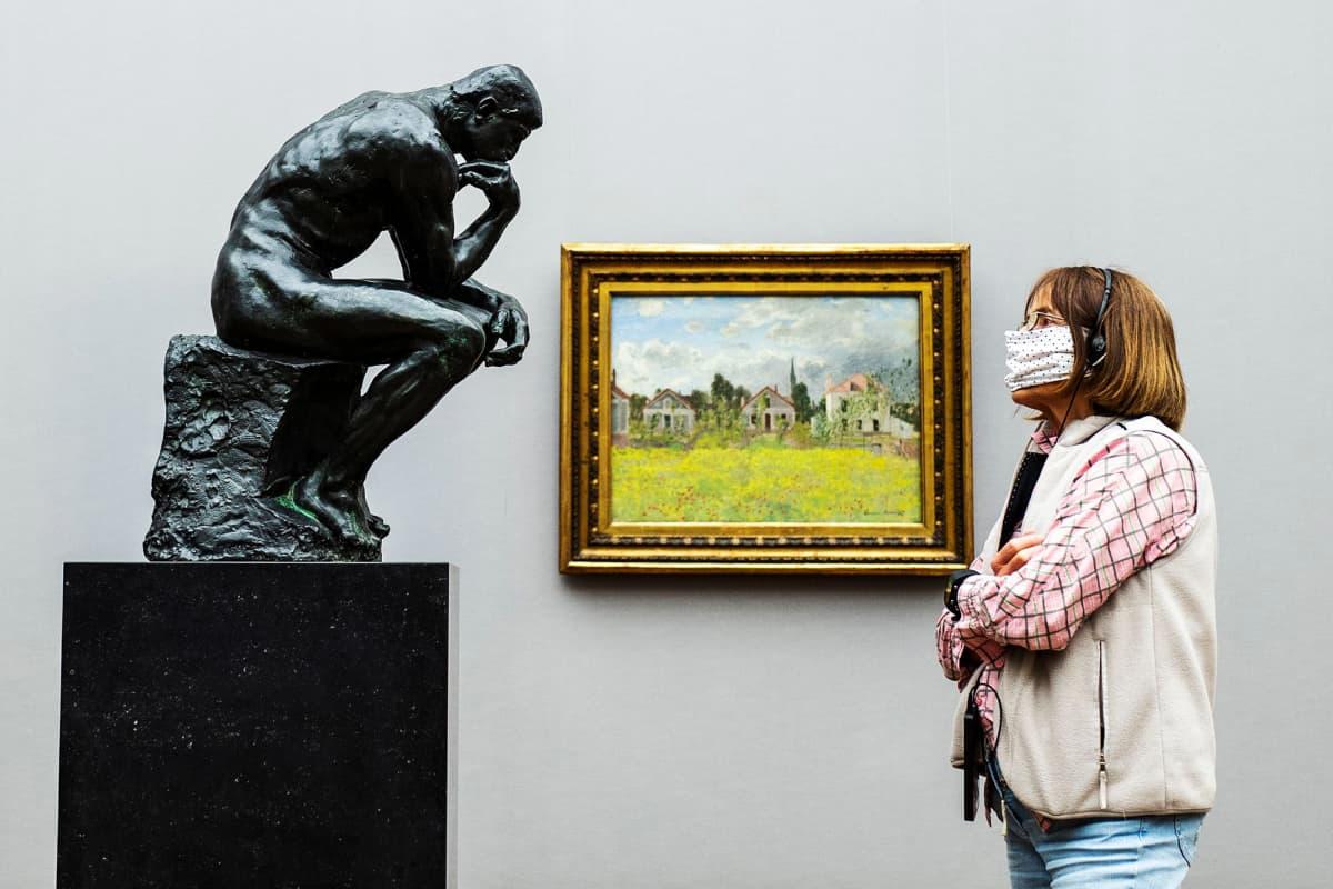 Kuvassa hengityssuojainta käyttävä nainen katsoo Rodinin Ajattelija-patsasta Berliinissä.