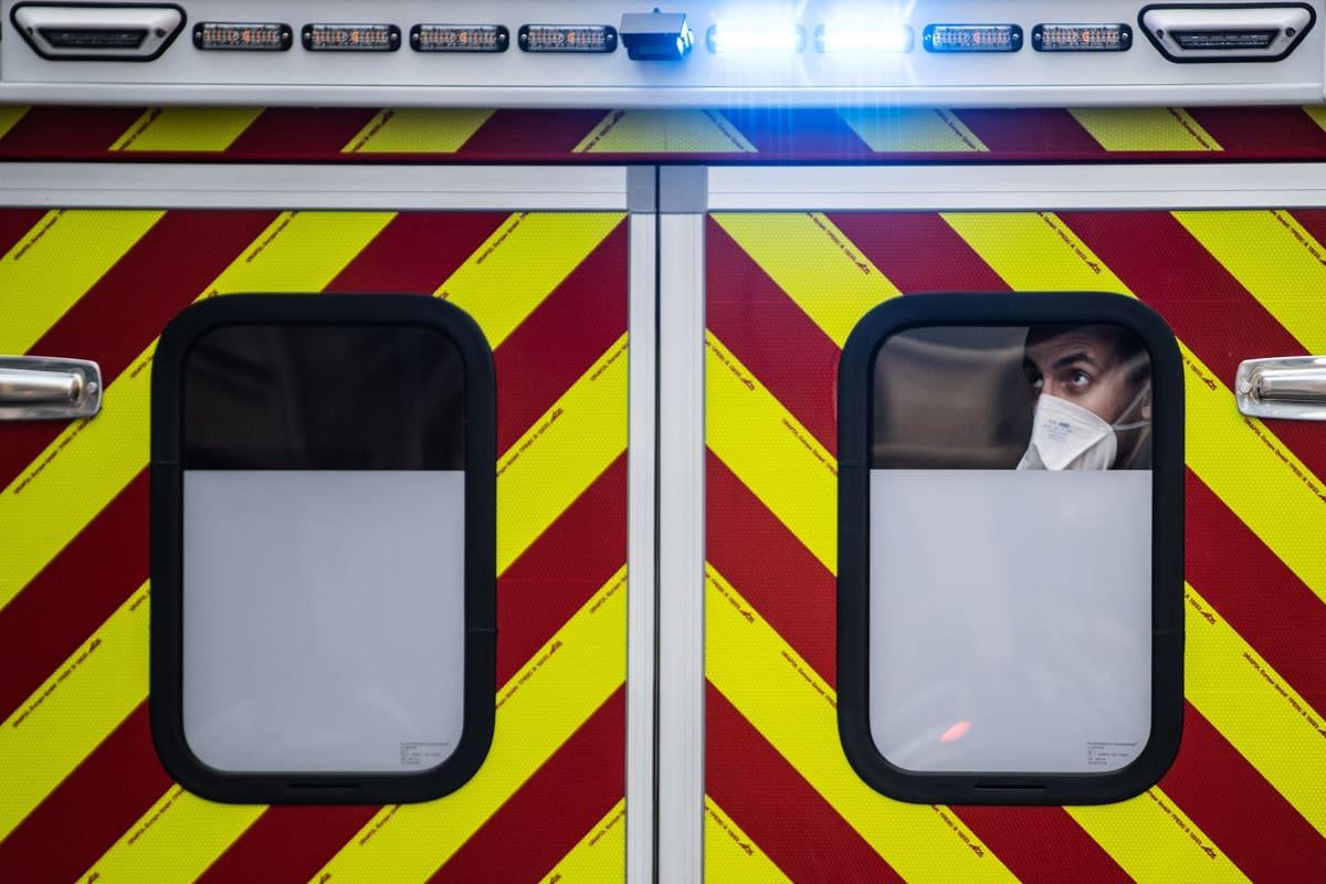 Kuvassa on hälytysajoneuvon ikkuna, josta kurkistaa pelastaja.