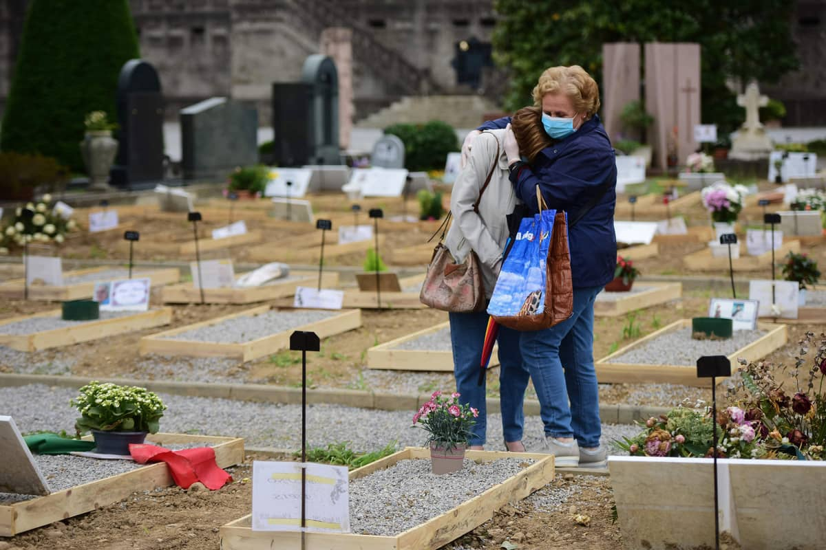 Kuvassa läheiset surevat haudalla Italiassa.