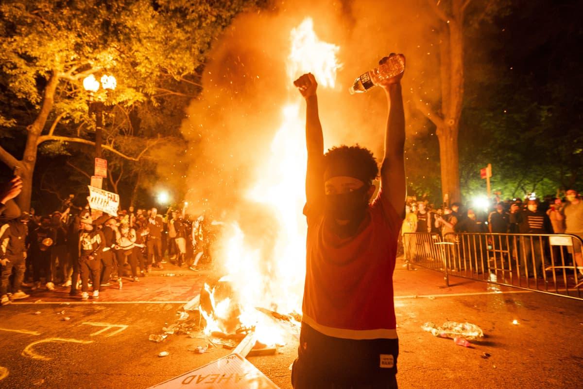 Mielenosoittaja tulipalon edessä.