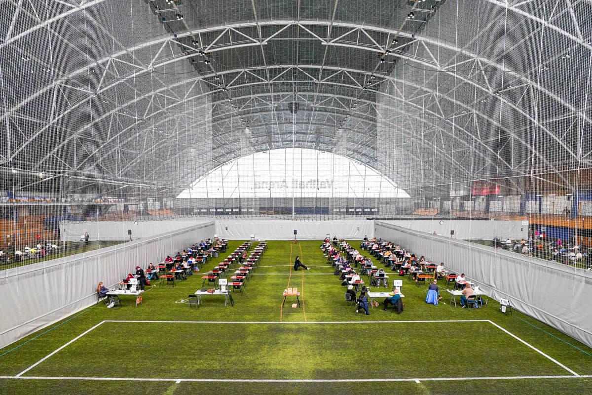 Kuvassa norjalaiset opiskelijat tekevät lukukauden päättökoetta väljästi isossa urheiluhallissa.