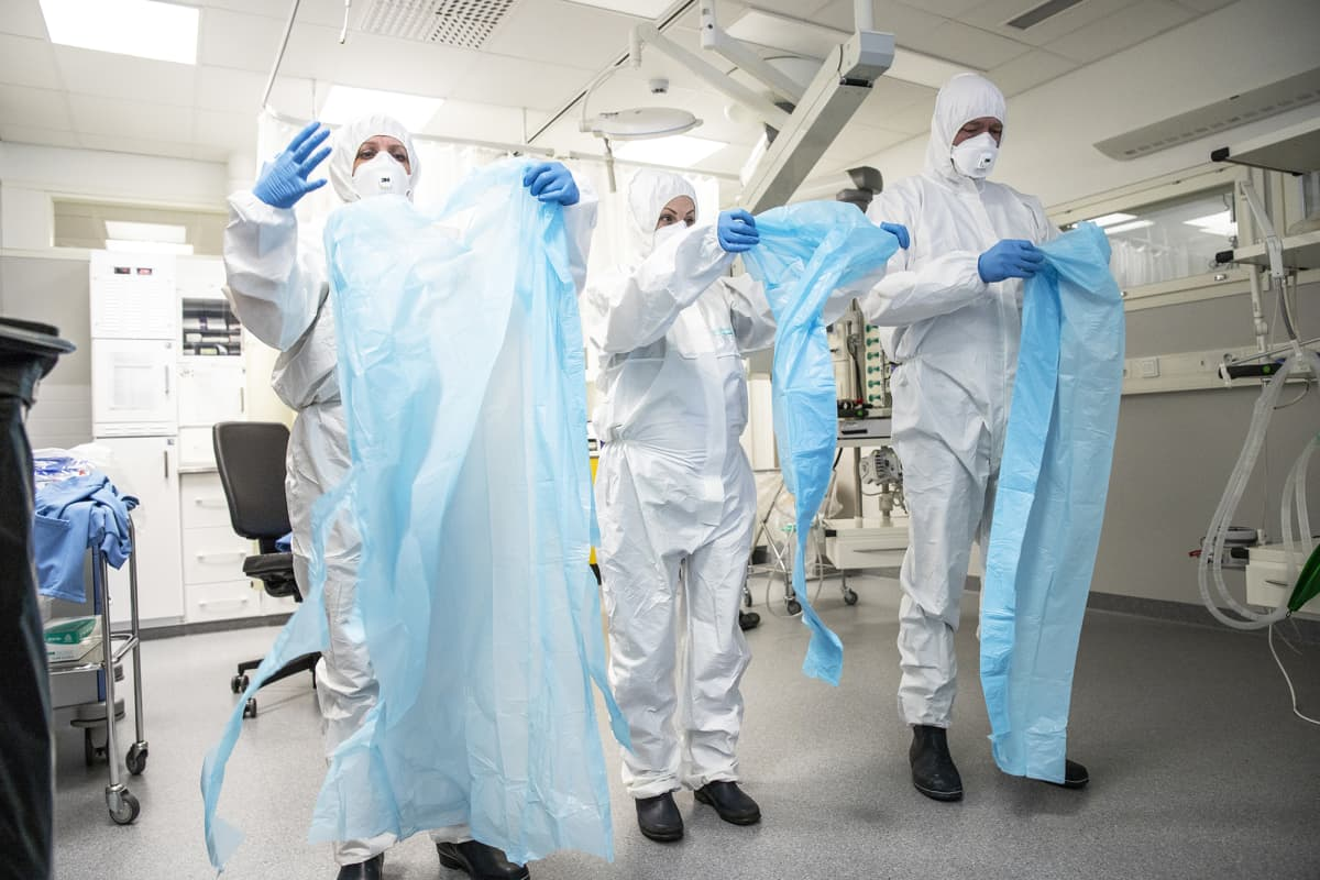 Sairaalahenkilökunta harjoittelee suojapukujen pukemista.