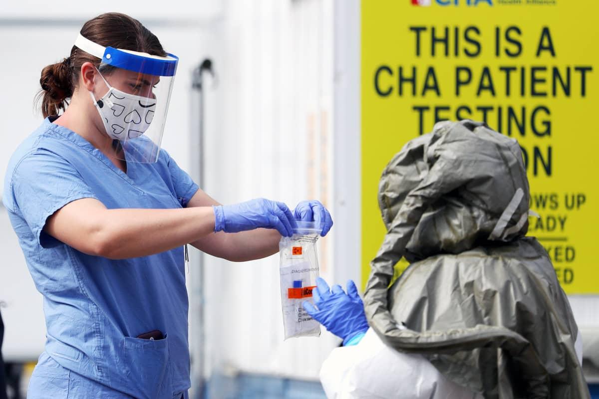 Suojavarusteisiin pukeutuneet työntekijät työskentelevät koronavirustestiasemalla.