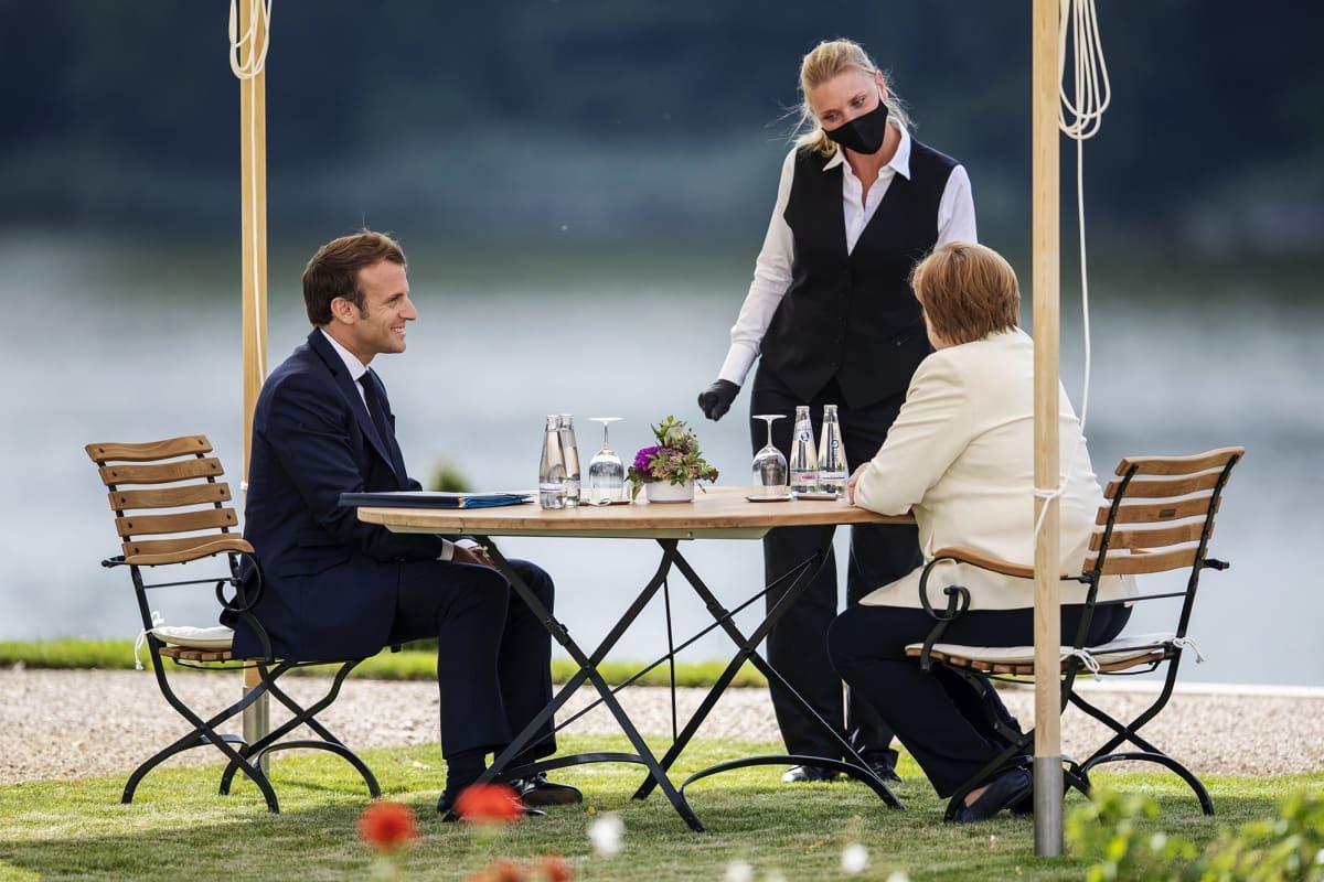 Kuvassa ovat Emmanuel Macron, Angela Merkel ja mustaa hengityssuojainta käyttävä tarjoilija.