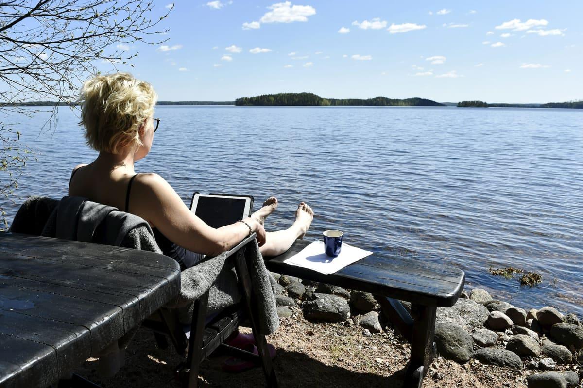 Kuvassa nainen tekee etätöitä järven rannalla.