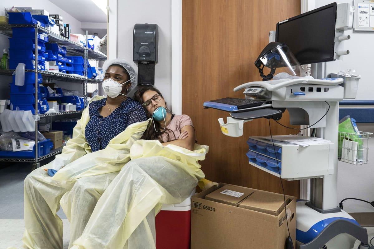 Tehohoidon työntekijät lepäävät sairaalan käytävällä Texasin Houstonissa.