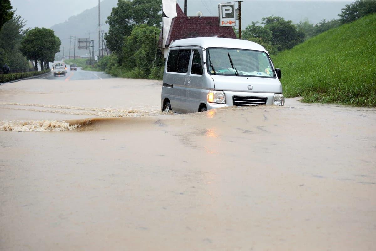 Pieni japanilainen pakettiauto tulvaveden saartamana maantiellä.
