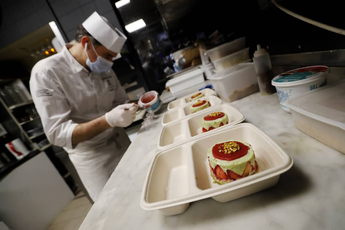 Kuvassa kokki Guillaume Arrago valmistelee noutoruoka-annoksia.
