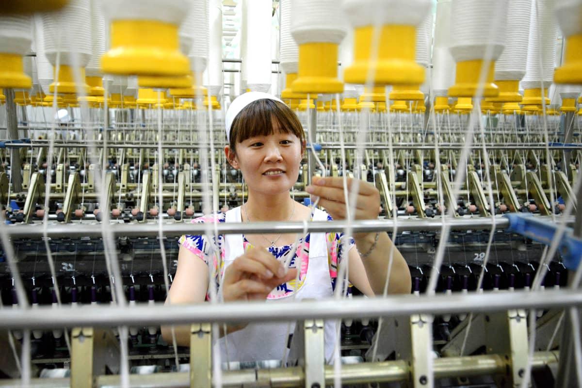 Kuvassa nainen kutoo Kiinassa.