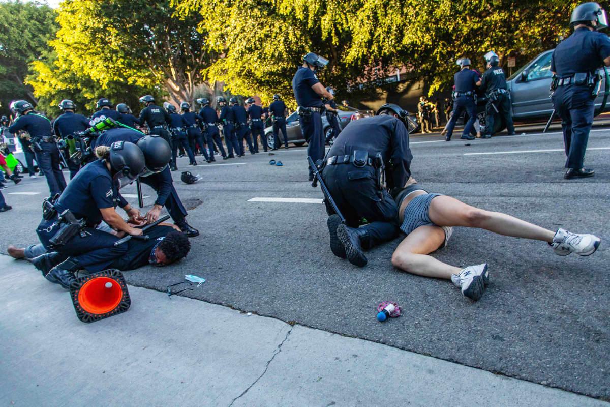 Poliisit taltuttavat kovin ottein mielenosoittajia.