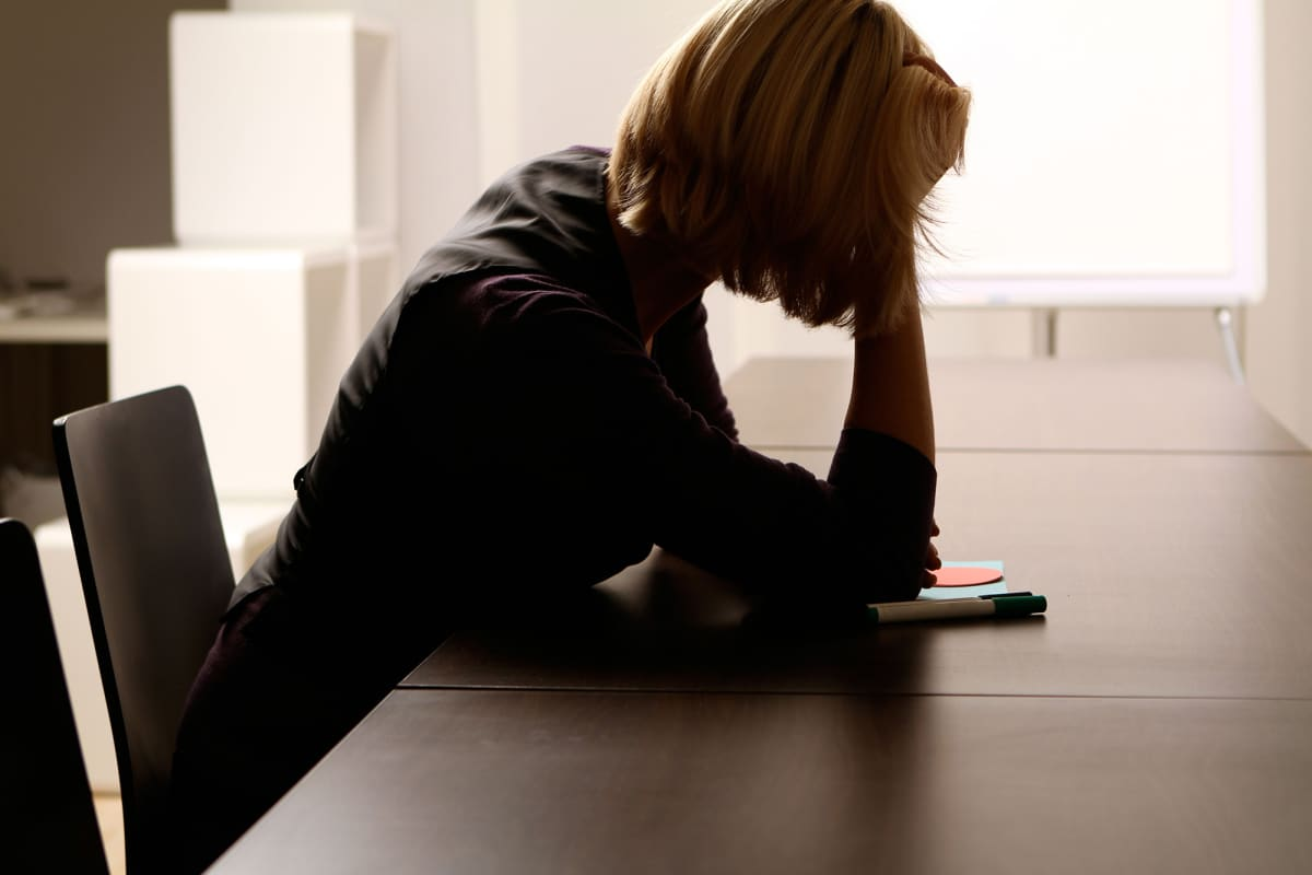 Nainen nojaa käteensä tyhjän kokouspöydän äärellä.