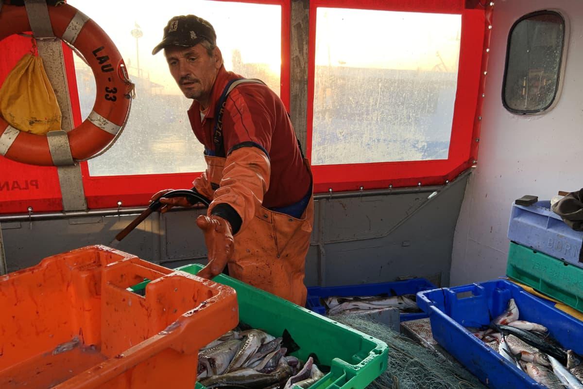Paikallinen kalastaja purkaa päivän saalista kalastaja-aluksen sisällä.