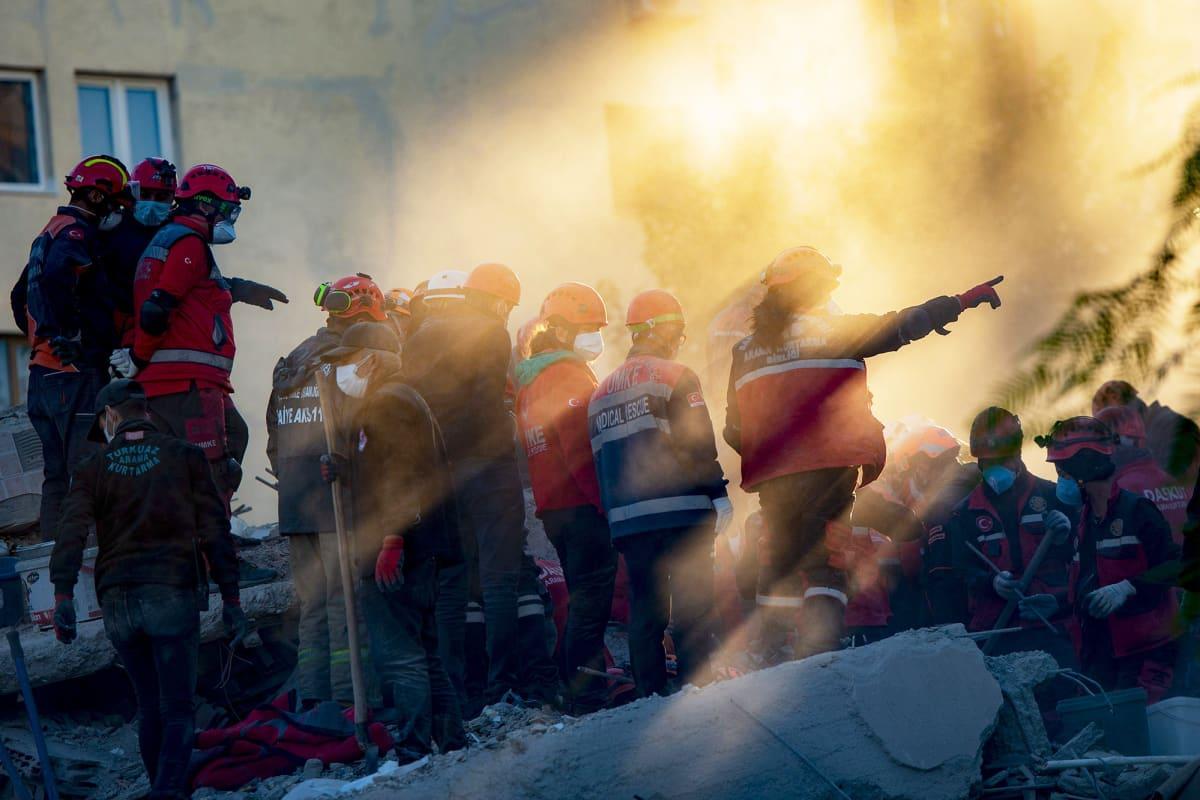 Pelastustyöntekijät ja vapaaehtoiset etsivät raunioista eloonjääneitä Turkin Izmirissä.