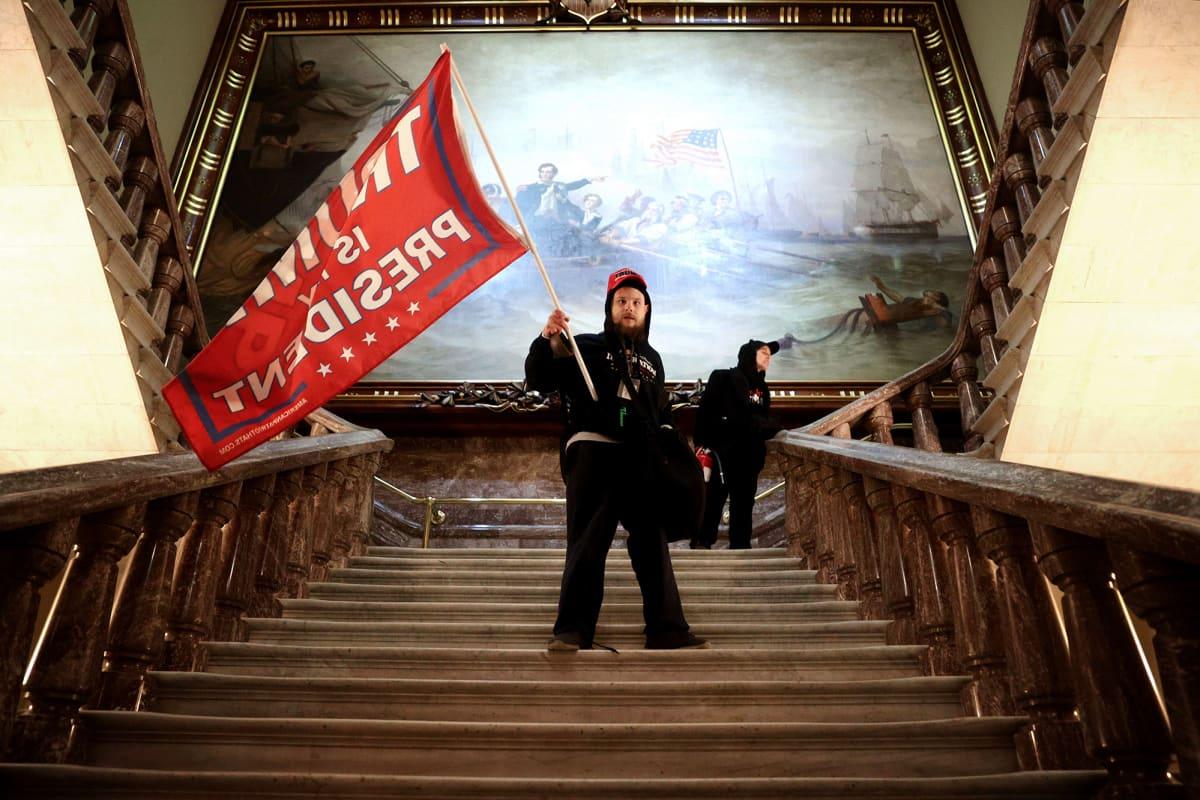 Mielenosoittaja heiluttaa lippua Yhdysvaltain kongressitalossa Washington DC:ssä.